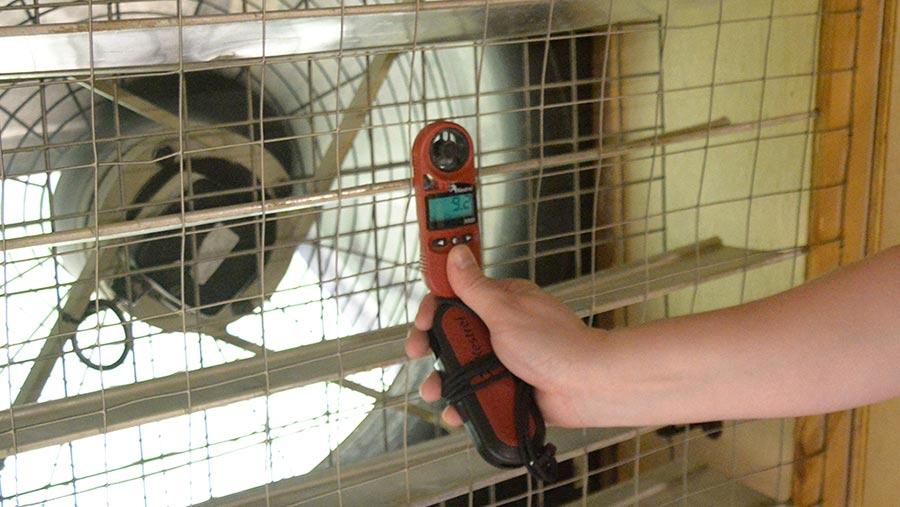 Hand holding a wind meter beside an industrial fan