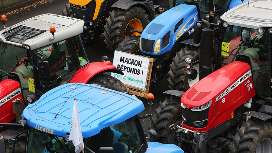 French farmers block the Parisian ring road with their tractors displaying placards reading 'Macron, answer!'