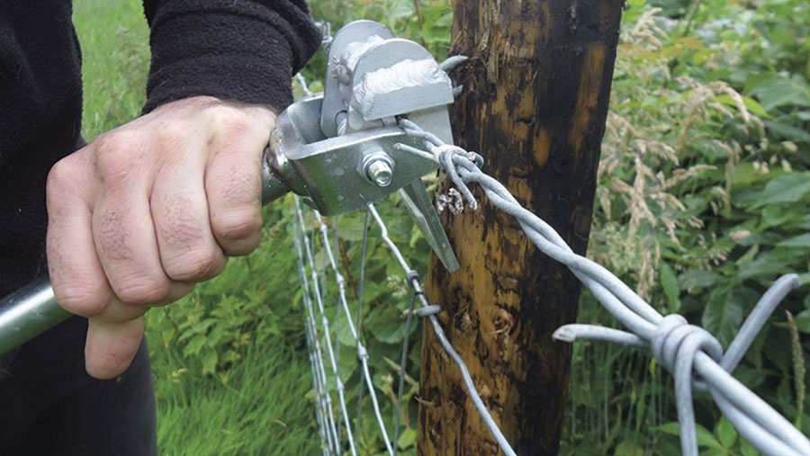 Close-up of staple puller working on a fence