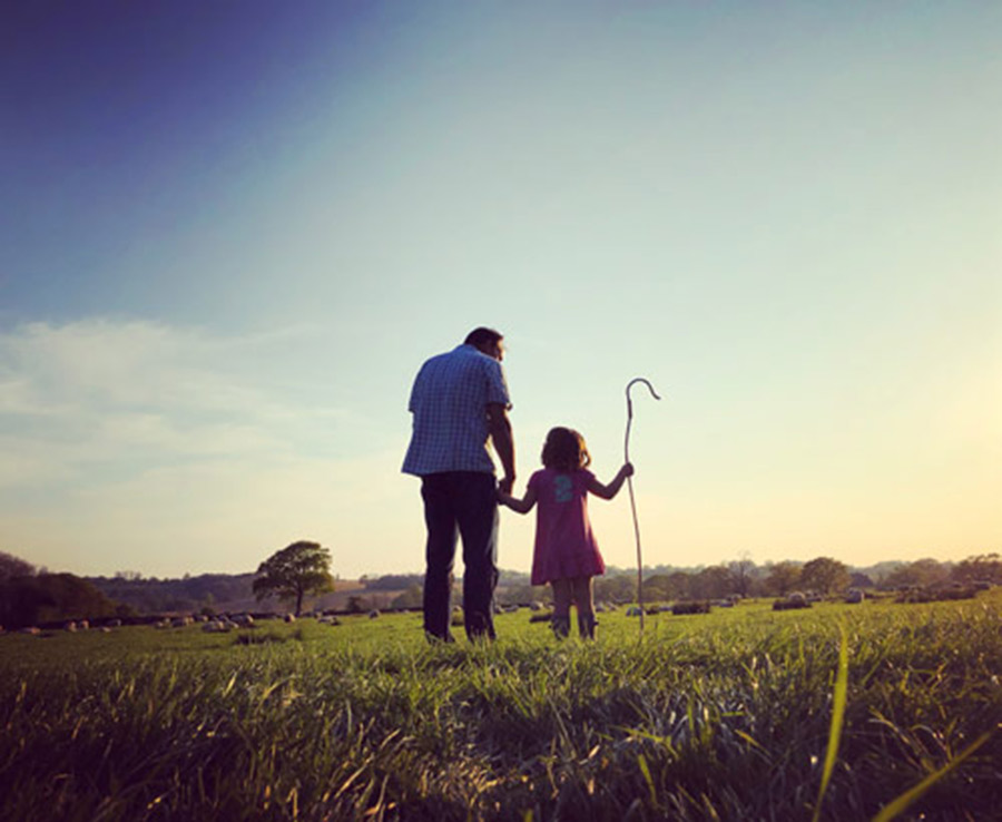 Girl with crook standing with dad in field