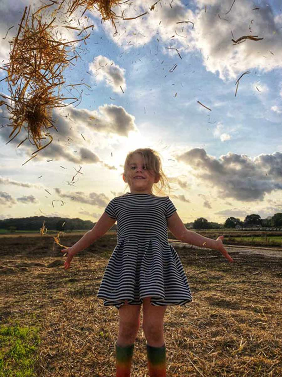 Girl jumping in field with hay in the air