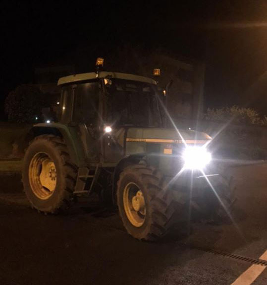 Tractor on road at night