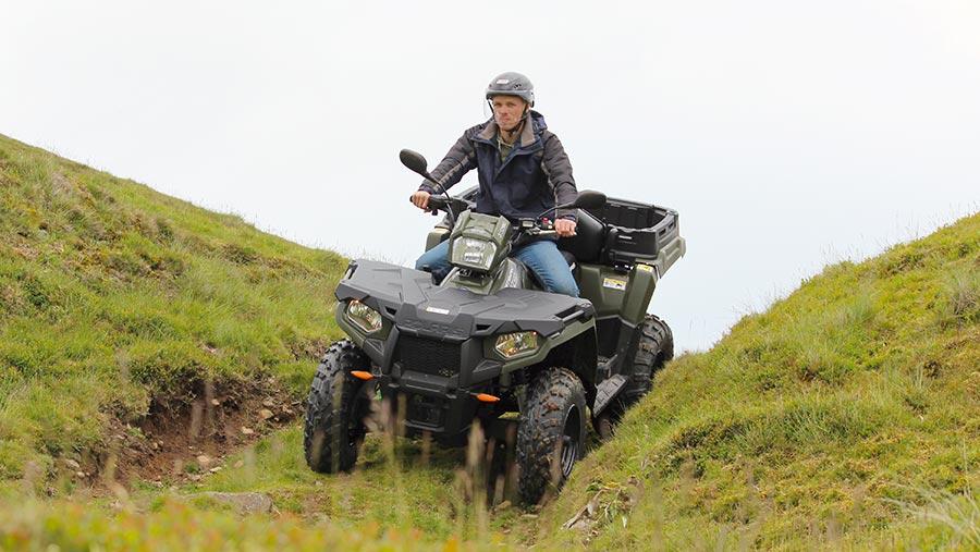 Man riding ATV in field