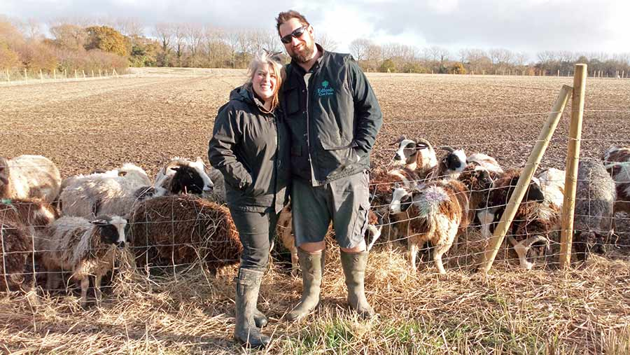 Chris and Louise Bishop-Howes standing in field with livestock