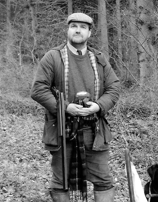 Charlie Flint stands near a wood with shotgun and ear defenders