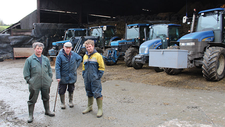 Paul, John and Andrew  Gould  standing in front of machinery shed