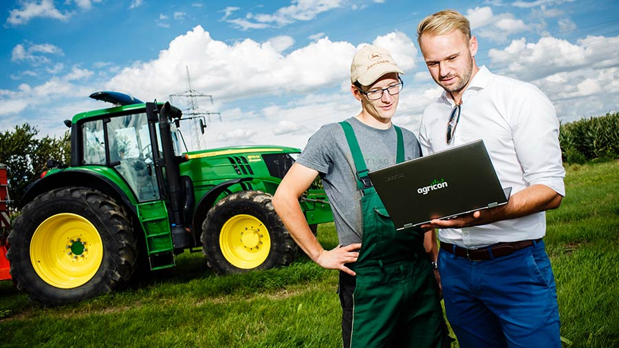 Two men looking at an Agricon laptop in front of a John Deere tractor