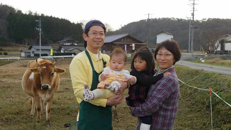 Masashi and Yuko Oda with their children and one of their Jersey cow