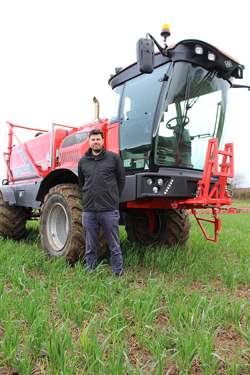 Chris Owen standing next to his Sands sprayer