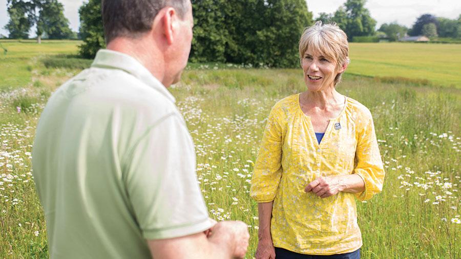 Alison Cross in a field with farmer