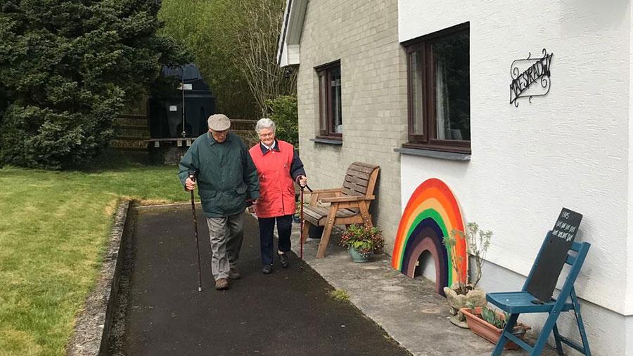 Rhythwyn Evans and his wife walking around bungalow