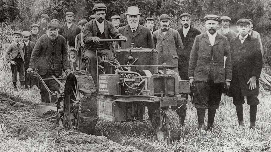 Men wearing plus-fours and flat caps surround a tractor