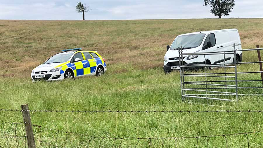 Police car and a white van in a field