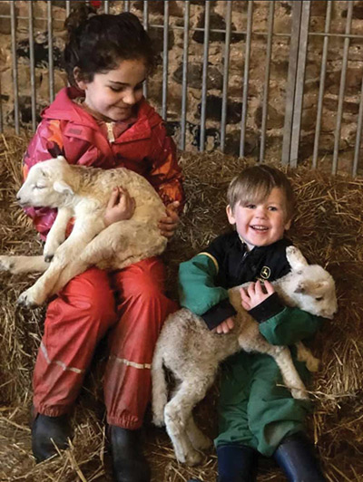 Daisy and Hamish holding lambs