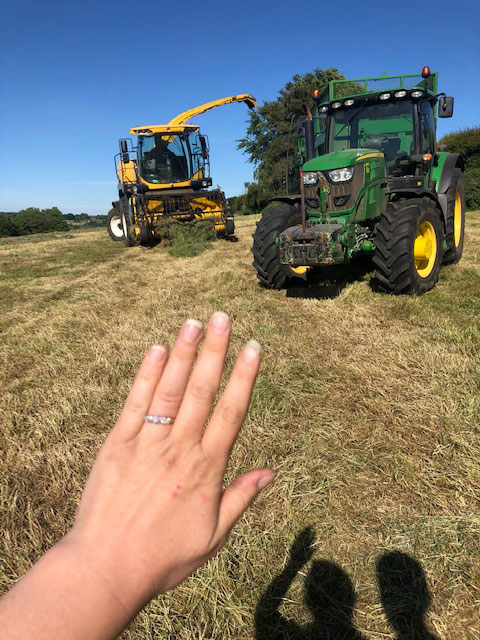 Hand with engagement ring and tractors in background