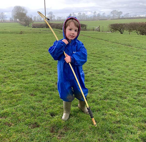 Four-year-old Jack helping his grandad move sheep and lambs.