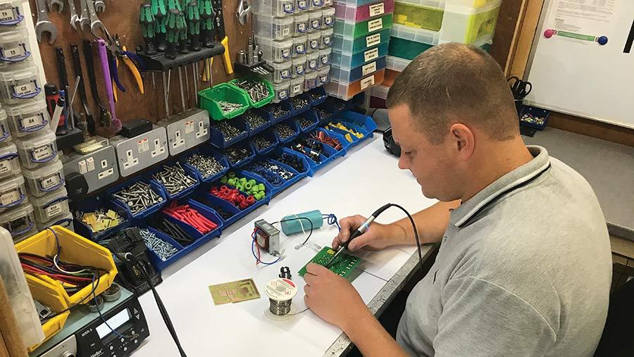 Arran Lange sitting at desk repairing panel