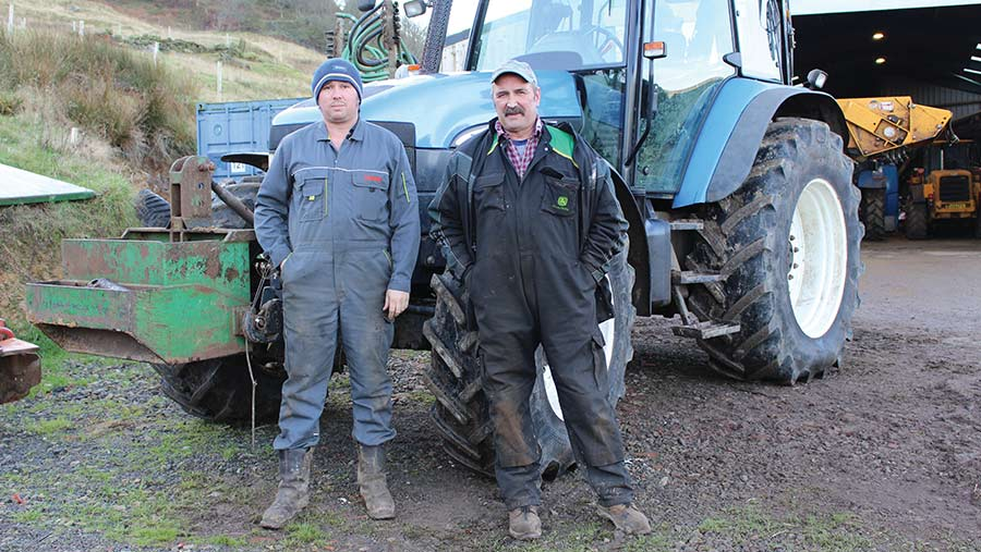 Two men stand beside a tractor