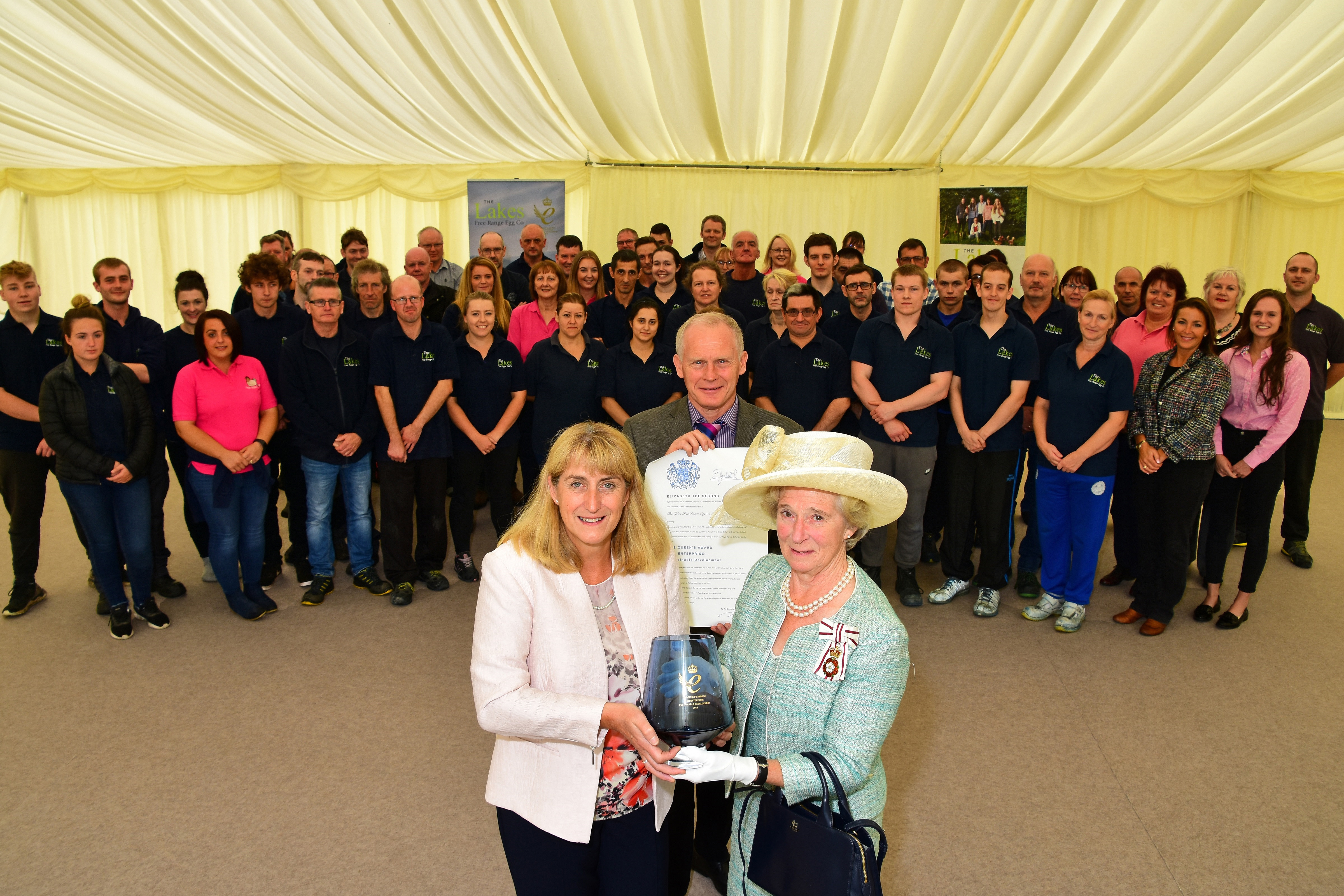 David & Helen Brass receive their award from Claire Hensman, Cumbria's Lord Lieutenant with staff helping celebrate.
