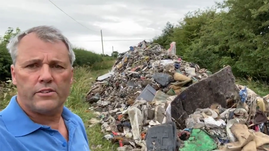 Andrew Ward next to fly-tipping