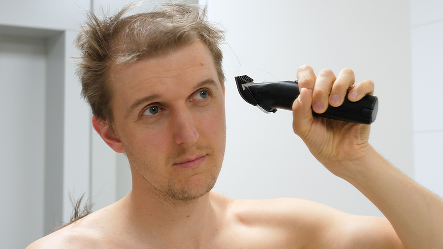 Young Man Cutting His Own Hair With A Clipper During Coronavirus Quarantine