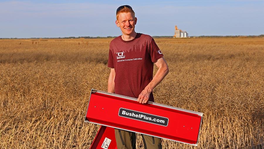 Marcel Kringe holding Bushel Plus system in field