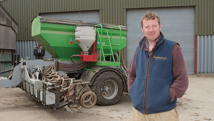 David Lord in front of farm machinery
