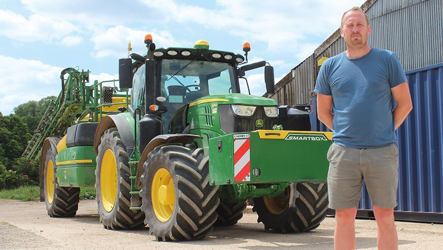 Tristan Newens standing next to tractor