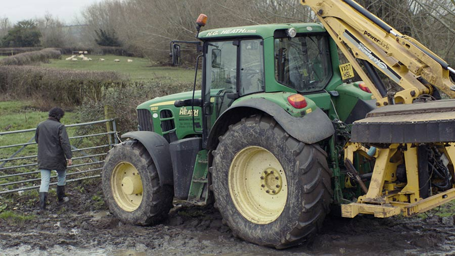 Tractor with a hedgetrimmer attached
