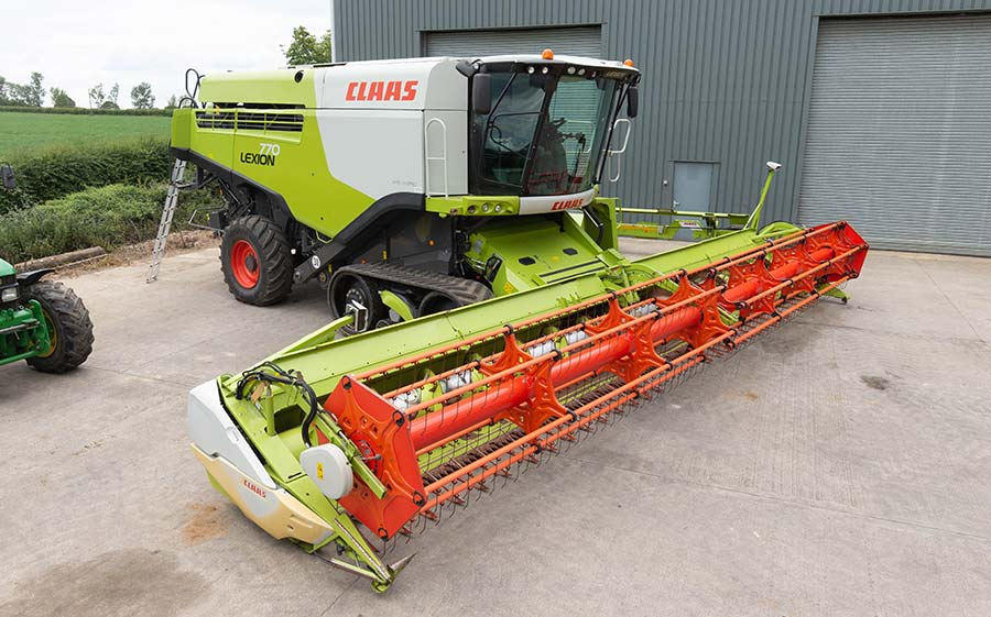 Combine in front of a barn