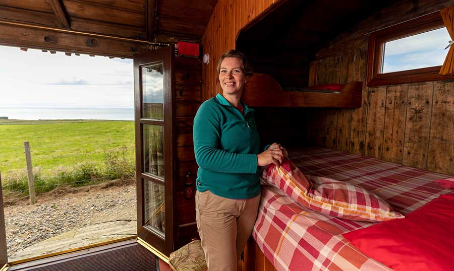 Carole Short making the bed in a cabin
