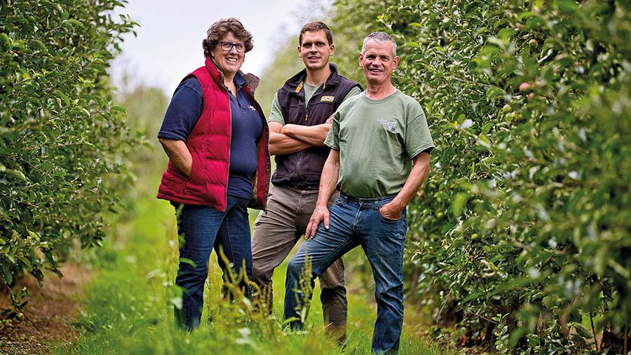 Esther, Henry and Monty Rudge standing in orchard