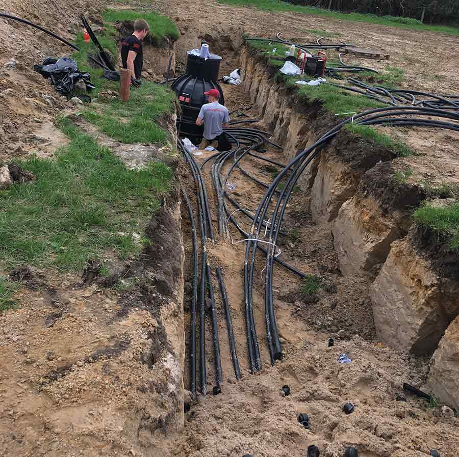 Trench in a field with people laying plastic pipes