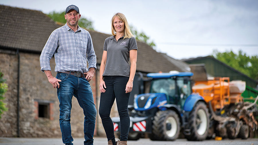 Julie and Tom Davies standing in farmyard with tractor