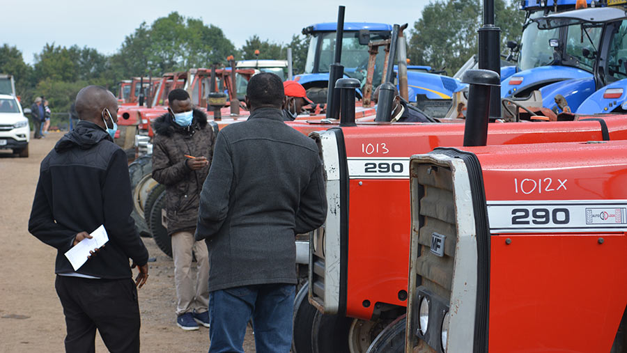 People in masks looking at tractors