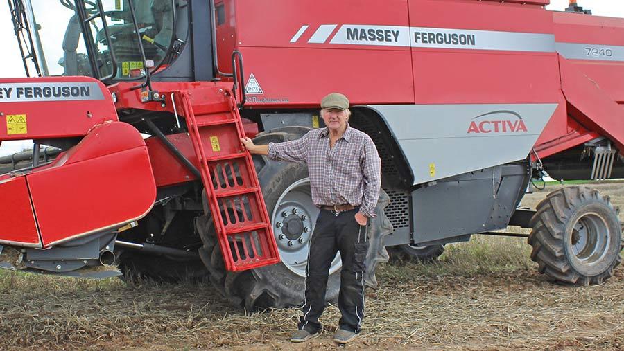 John Roberts stands beside his combine