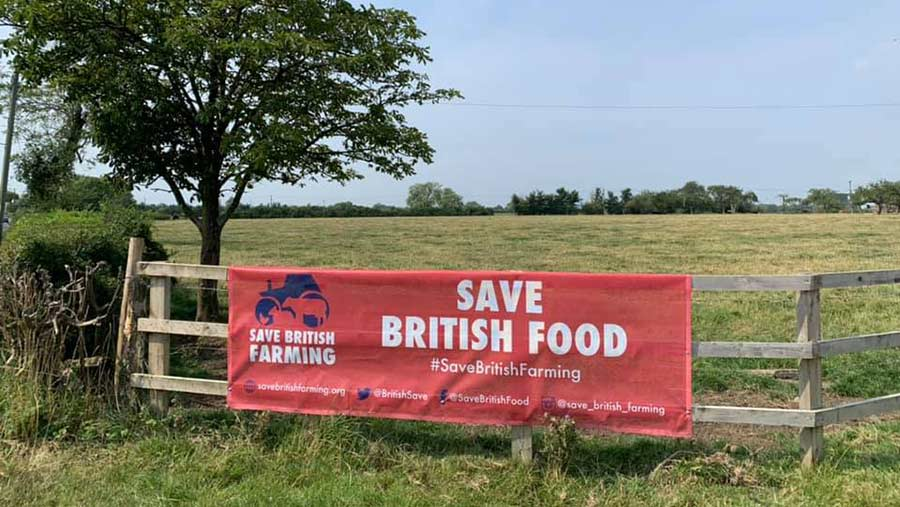 Banner on a farm fence reads Save British Food