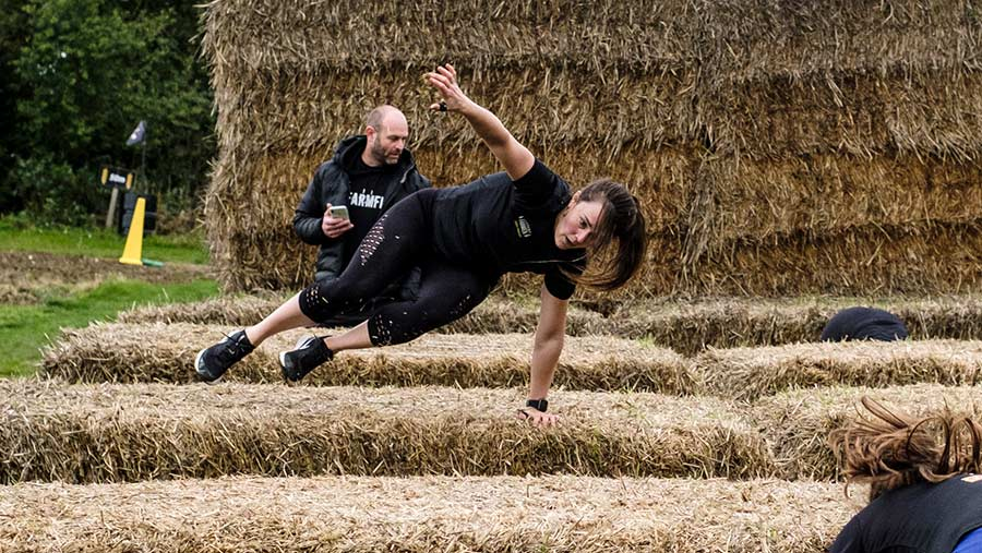 Britain's fittest Farmer 2020 winner Emma Ashley leaps over a bale © Colin Miller/MAG