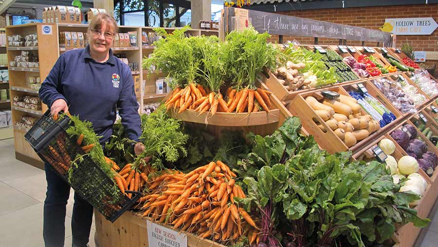 Sally Bendall with in farm shop with vegetables