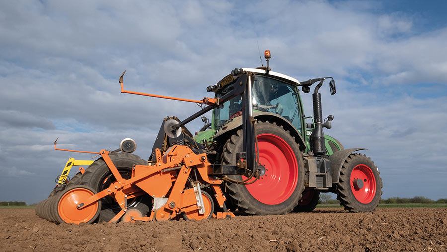 Tractor drilling sugar beet in field