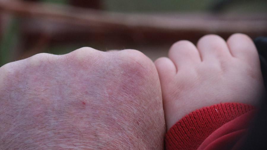 Man's hand next to child's hand