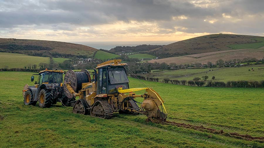 Installing cable across grassland