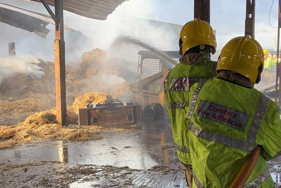 Two firefighters hose down burning hay
