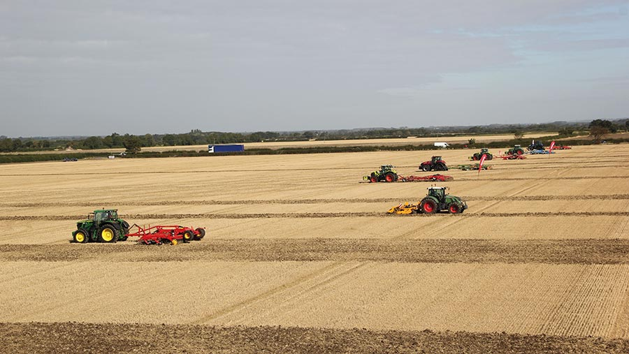 A row of tractors and cultivators in a large field