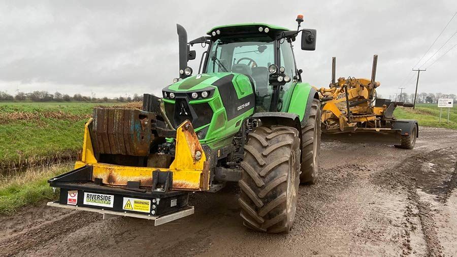 Tractor towing farm track grader