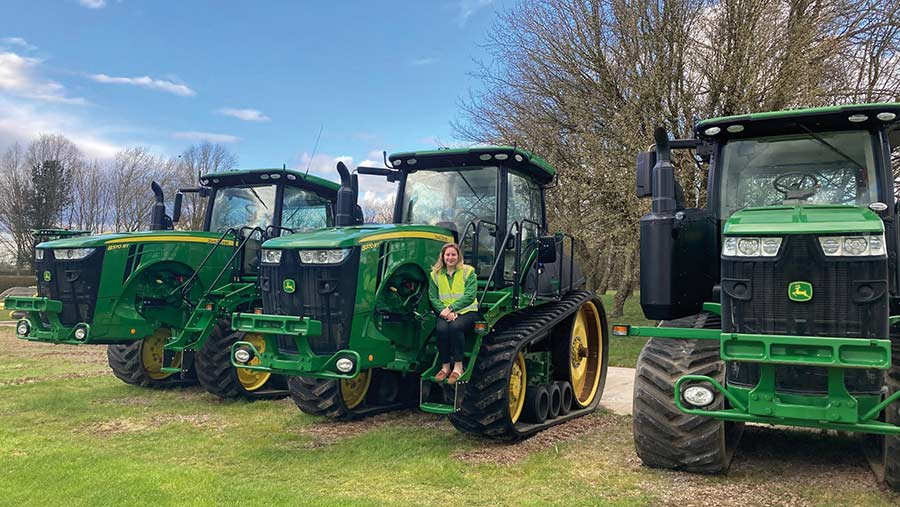 Masie Wildgoose next to John Deere tractor