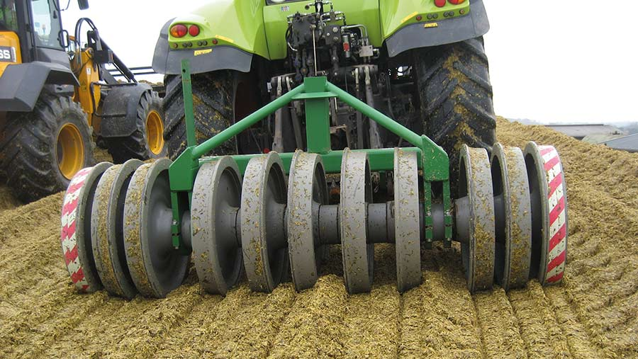 Tractor with a Silopactor being used to roll a clamp