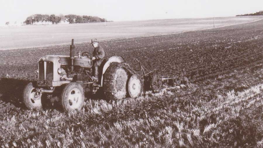 Old black-and-white picture of a man ploughing wearing a trilby hat