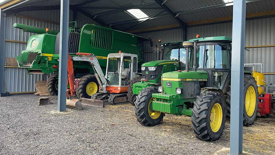 Combine, digger and tractors in farm shed