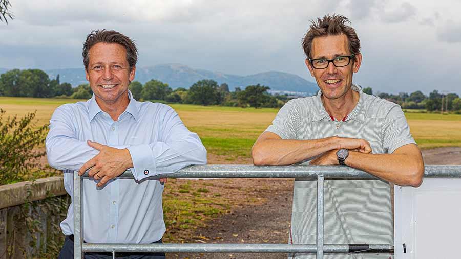Two men lead on a farm gate
